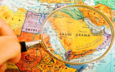 Studying Geography - Looking through magnifying glass at Saudi Arabia on a globe.