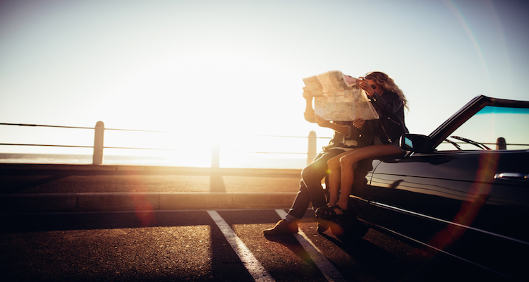 Hipster couple planning their summer seaside road trip with convertible
