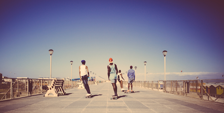 African American teenagers longboarding on a walkway at the beach